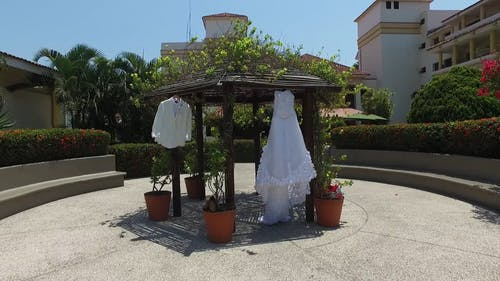 White Wedding Dress and Suit Hanging in the Gazebo