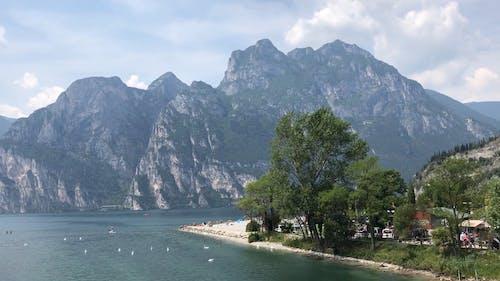 Scenic View of the Mountain Range in Lake Garda with People on Kayak