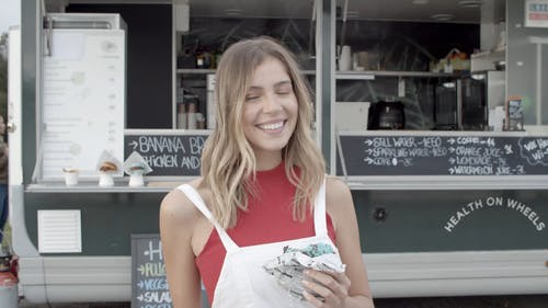 Blonde Woman Eating a Burger In Front of a Food Truck