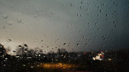 Close Up View of Raindrops and Lightning on a Glass Window