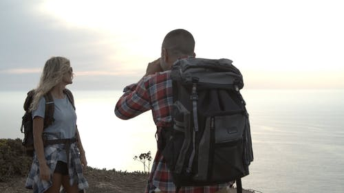 Two Backpackers Taking Photos by the Ocean