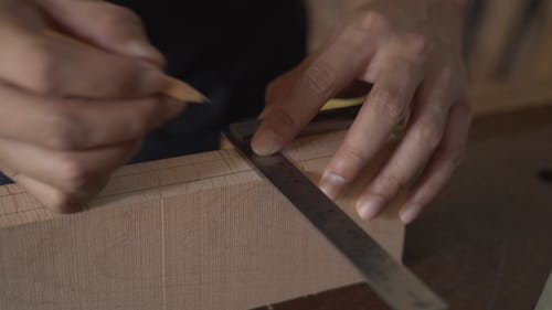 A Person Marking Measurement On A Lumber Wood