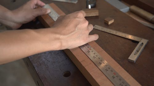 A Person Measuring Wood