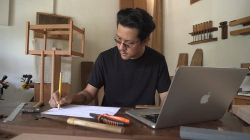A Man Using a Laptop While Writing
