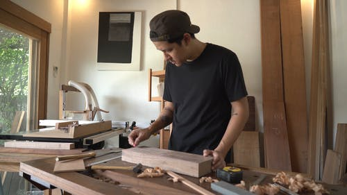 A Man Marking a Lumber Wood