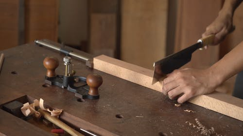 A Person Using a Hand Saw on Wood