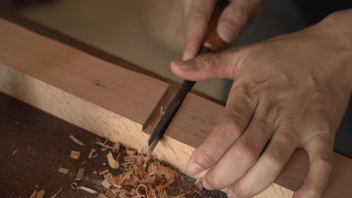A Person Using a Chisel on Wood
