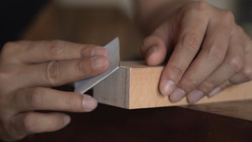 A Person Sanding the Edge of a Wood