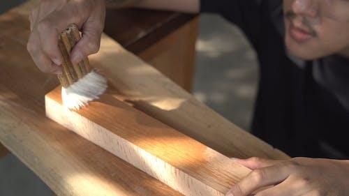 A Man Brushing A Lumber Wood