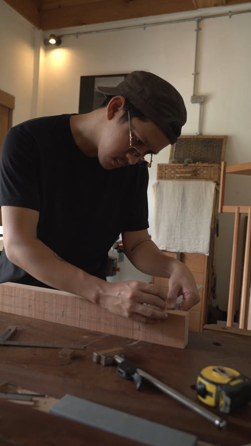 Man Smoothening Edges of a Wooden Block
