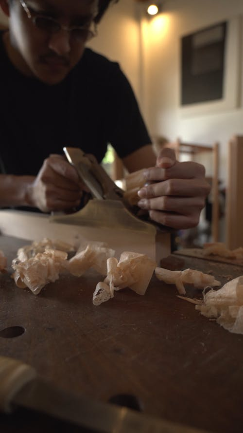 A Man Using a Hand Planer on a Lumber Wood