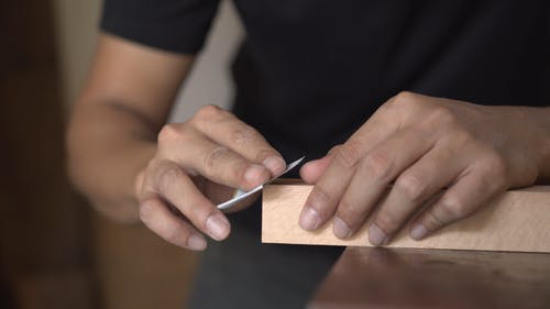 Working on a Wooden Plank With Sandpaper