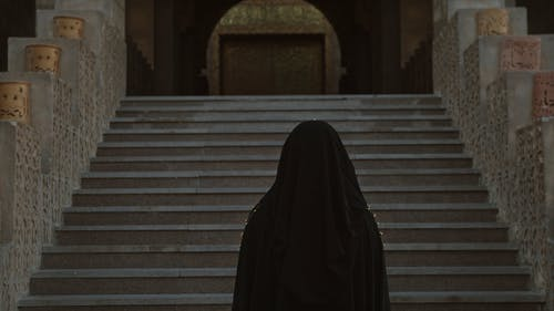 A Woman In Hijab Going Up The Mosque Stairs