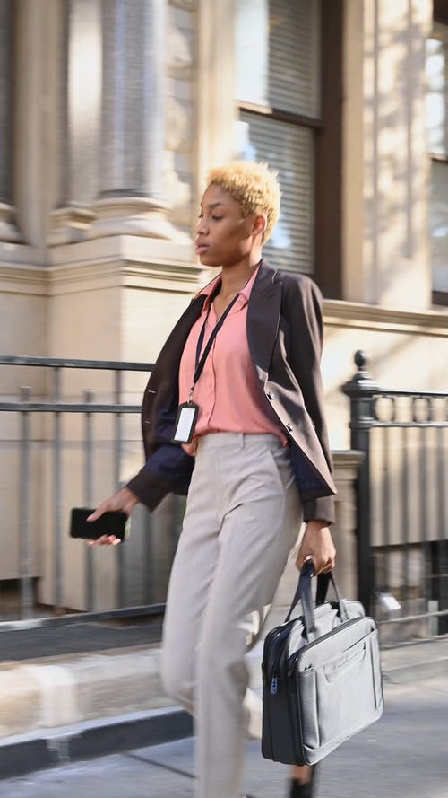A Woman In Business Attire Walking In The Sidewalk