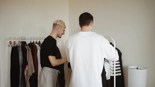 Back View of a Couple Choosing Clothes From the Rack