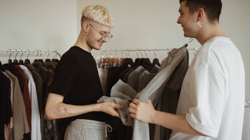 A Couple Fitting Clothes from the Clothing Rack