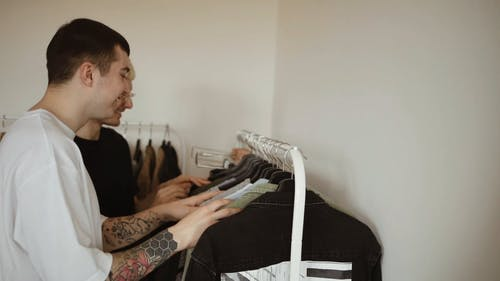 A Couple Choosing Clothes from the Clothing Rack