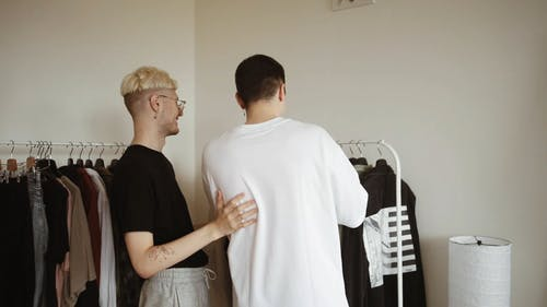 Back View of a Couple Picking Clothes from the Clothing Rack