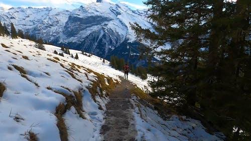 A Man Running Down a Snowy Mountain
