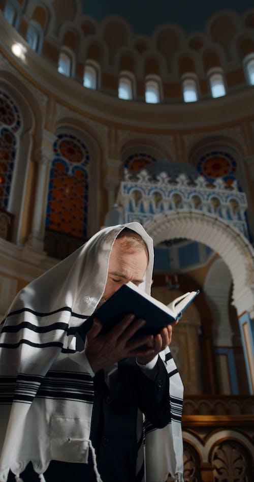 A Jewish Man Praying and Reading the Bible While Swaying