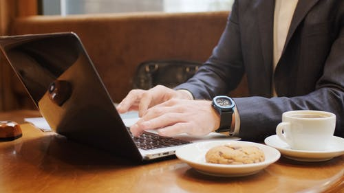 A Person Typing and Using His Laptop