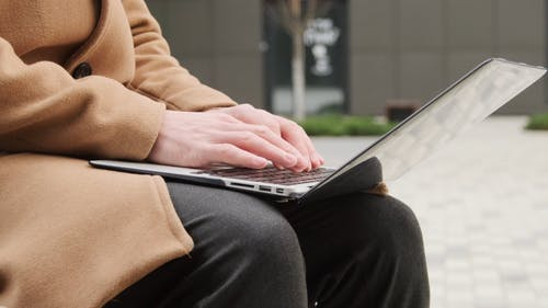 A Person Busy Typing and Using His Laptop