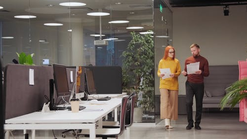 Colleagues Discussing a Documents While Walking Inside the Office