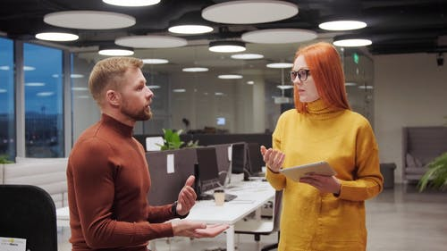 Man and Woman Talking to Each Other Inside the Office