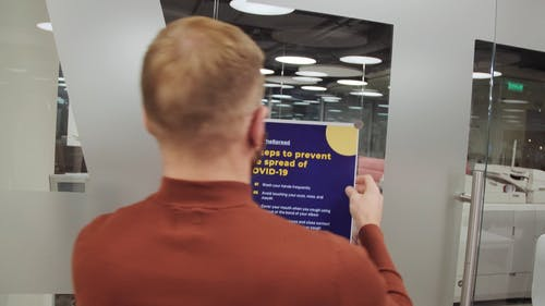 A Man Posting a Covid-19 Awareness Poster on a Glass Wall