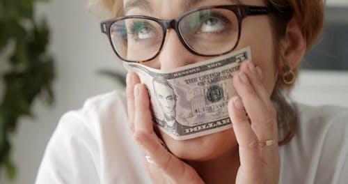 A Woman Smelling Dollars Bill
