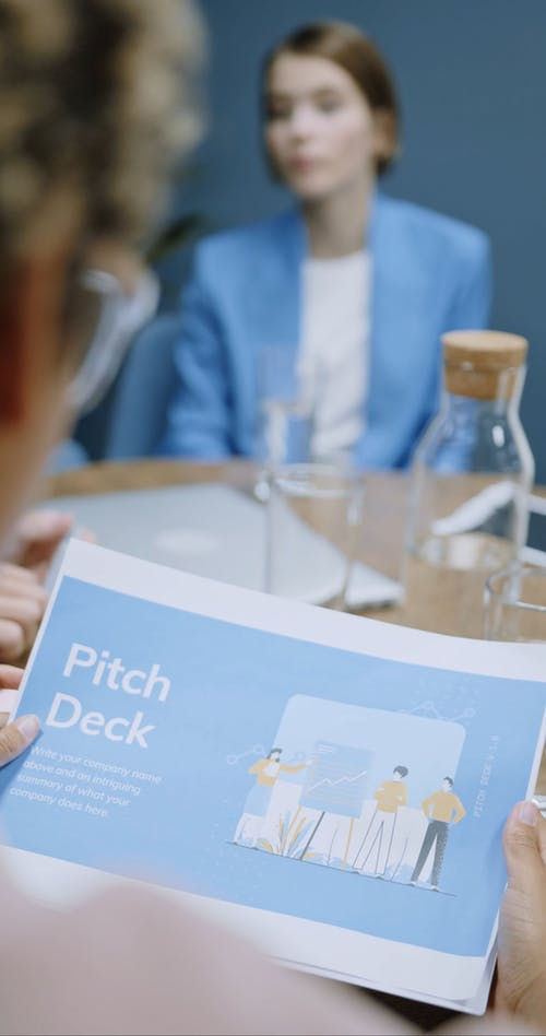 A Woman Looking At Printed Documents In A Meeting