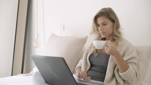 Woman Busy Using Her Laptop While Drinking Her Coffee