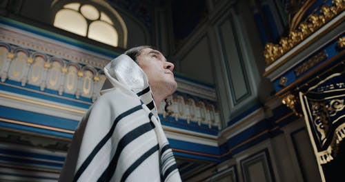Low Angle View of a Man Wearing Tallit Looking Upwards then Looks at the Camera