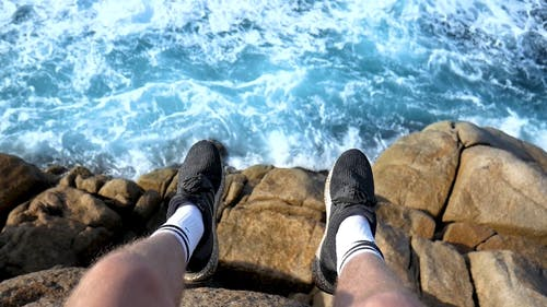 Person in Black and White Sneakers Sitting on Brown Rock Near Blue Sea