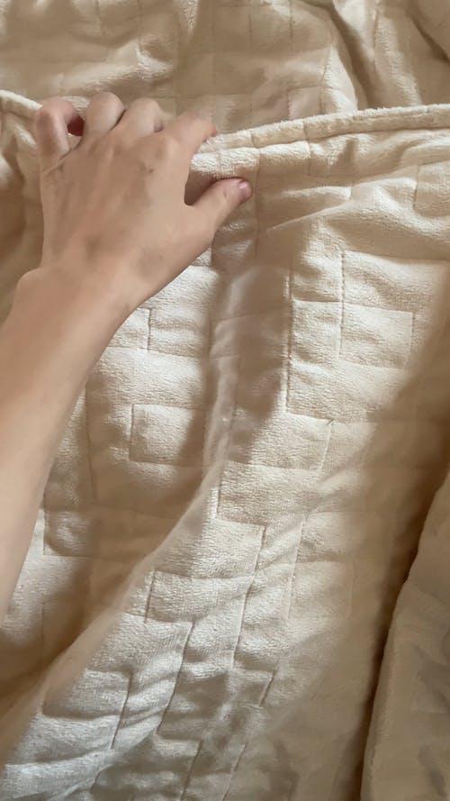 ベッドシーツの下で眠っているペット
