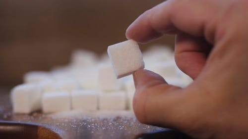Close Up of a Person Holding a Sugar Cube