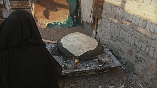 A Woman Cooking A Flat Bread