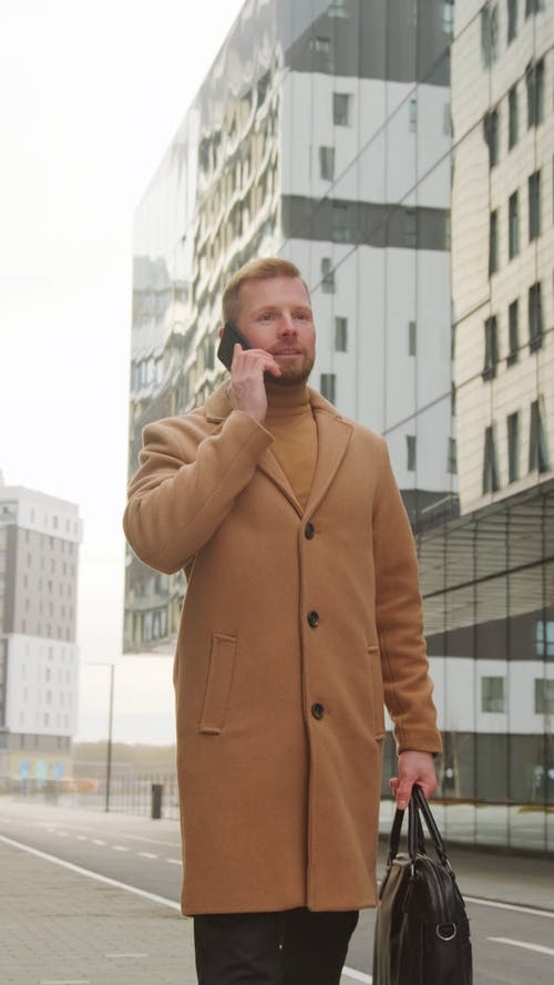 Man in Brown Coat Walking Outdoors While Talking on the Phone