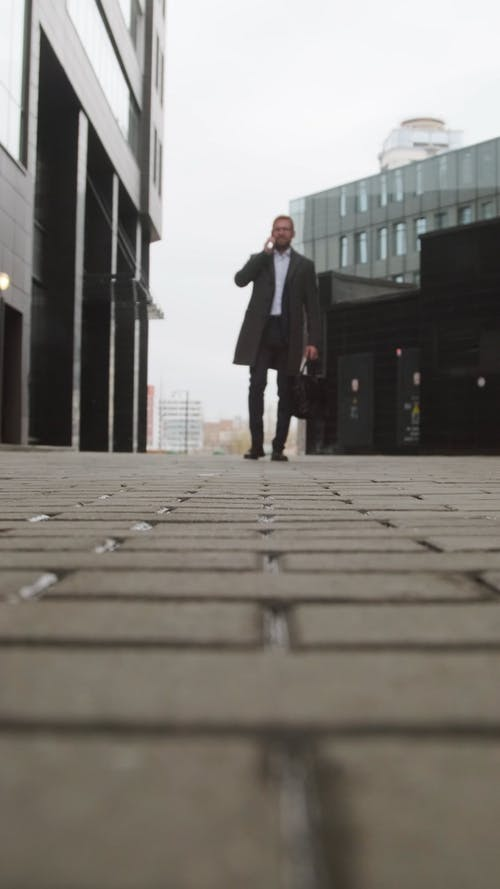 Low Angle View of a Man Walking Outdoors While Talking on the Phone