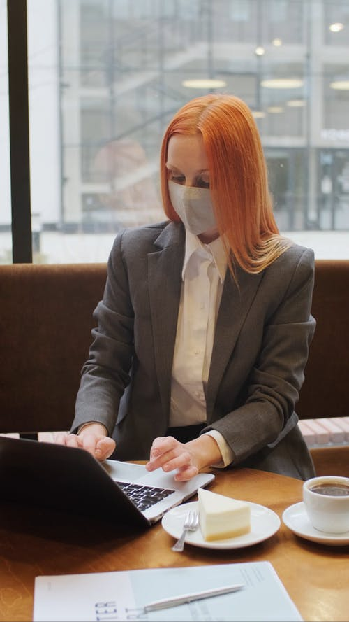Woman Wearing a Face Mask While Typing Using Her Laptop