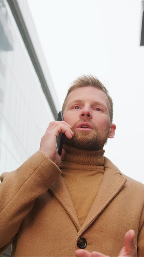 Man in Brown Coat Talking on the Phone