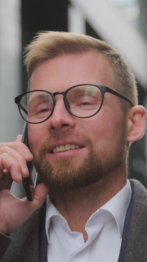 Man Wearing Eyeglasses While Talking on the Phone