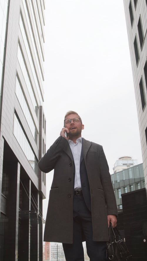 Man in Gray Coat Standing Outdoors While Talking on the Phone