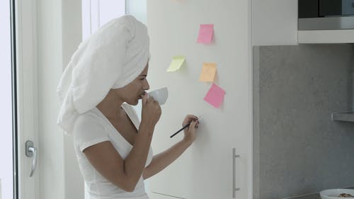 A Woman Writing Notes On Stick Pads