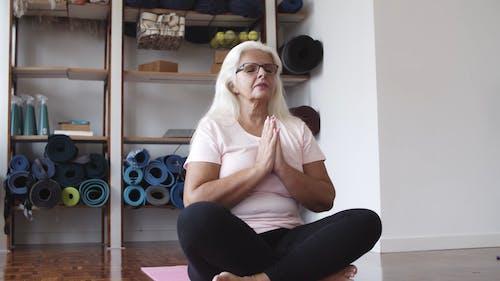 Elderly Woman Meditating and Practicing Yoga