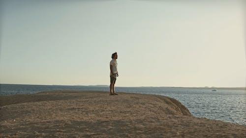 Man Standing on Cliff Coast