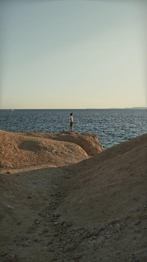 Man Standing on Cliffside