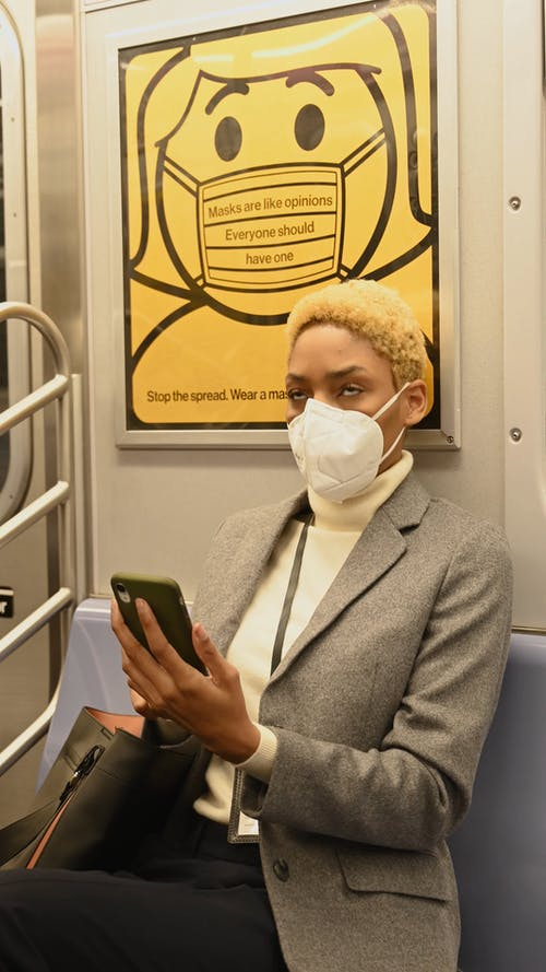 Woman Sitting Inside a Train While Using Her Smartphone