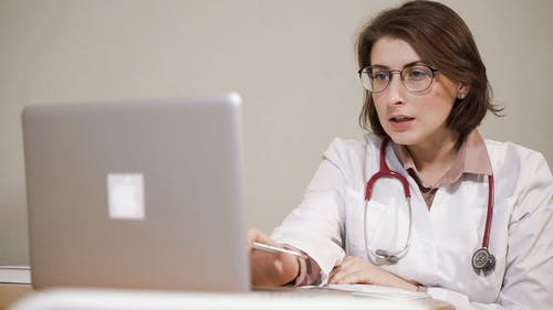 A Lady Doctor Using A Laptop For Her Work