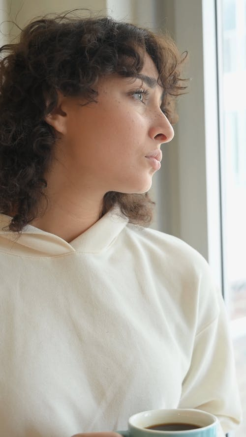A Woman Looking Outside The Window